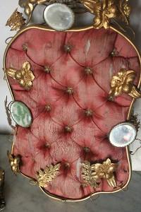 かなり古い時代の装飾的な小家具の一部と思われるお品です。  綿の入った布には花形のビスがはめられ、鏡やメタルの草花で飾られています。 メタルは薄めで、全体の重量もそれほどありません。 布は破れやヨゴレなどが目立ちます。鏡にはくもりが見られます。  威厳のある存在感は、古いものならでは。珍しいお品です。  たて31 横18