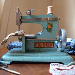 おもちゃのアンティークミシンです。  ブルーのメタルにバラのお花柄がレトロでとてもかわいいトイミシン。当時の糸がついています。インテリアのオブジェとしても存在感があり、子供部屋やショップに飾ってもすてきだと思います。  説明書通りに調節し、正しく使えば、実際に縫うこともできます。  サビ、欠けなどなく、コンディションは良好で、とてもきれいです。オリジナルの箱、説明書がついていますが、箱はカビ、破れ箇所あり、かなりお疲れです。  古いものなので、おもちゃとしての安全基準は現在のものとは異なります。お子様とご使用の場合は、安全には十分ご注意下さい。