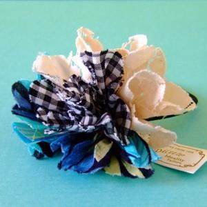 花型にカットしたチェック柄×リーフ柄×レースの 3種類の生地を重ねて咲かせた、 簡単アレンジにちょうど良い、ひらひら軽やかな花のヘアゴム。 ナチュラルスタイル・カジュアルスタイルに似合います。 髪からほどいて、手首につけてもかわいいですね。 カラーはブルー/パープル/グリーンの3色展開。