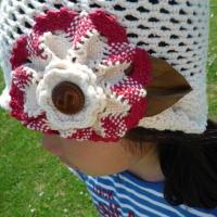 大きなお花に本革の葉っぱがポイント シンプル編み帽子の飾りは大きなレースのお花にビンテージのデットストックの革ボタンを載せました。  葉っぱは本革で、本物のように洗いをかけています。  お子様の帽子なので、手洗いできるように 葉っぱの部分はブローチになっており、取り外しできます。麦わらに載せてもかわいい葉っぱのブローチです。