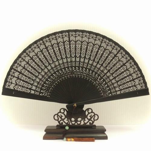 黒檀(烏木)から作られた扇子です。    本来、黒檀という木は非常に硬くて重い木なのですが、精巧な彫刻と研磨によって 重たさを感じさせない、洗練された作りになっています。 黒檀特有の綺麗な艶が出ています。   専用の扇子箱に入れた状態でのお届けとなります。   木材:黒檀(アフリカ) ※ 白檀とは異なり、黒檀には香りはありません   <<<黒檀マメ知識>>> 中国では「烏木(ウームー)」と呼ばれています。烏(カラス)のように真っ黒な木、という意味ですね。 熱帯を中心に、アフリカ、インド、インドネシア、スリランカ、タイ、ベトナム...と各地に分布しています。   日本と同様、「本黒檀」「条紋黒檀(縞黒檀)」などと分類されてはいますが、一般的には総称としての全ての黒檀を「烏木」と呼ぶ場合がほとんどです。 つまり、中国の木製品を販売している店で、「これは何の木ですか?」と聞いても、一般レベルの店員さんからは「烏木(黒檀)です」としか答えが返ってこない場合が普通です。 「何黒檀ですか?」という質問は、幅広い木材知識を持った人以外には使えません...   成熟した黒檀の樹は高さ25m、直径1mにもなるのですが、成長がとても遅いのが特徴です。 (この「成長の遅さ」が、木材としてのきめ細かさや固さに影響するのですけどね) 黒檀は白檀と異なり、芳香はしません。 産地によって「印度烏木」「台湾烏木」という呼び方をする場合もあるようです。