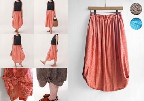 ブロックチェック模様が素敵な結びスカート ファーマーの働くシルエットから想い描かれたスカート 裾のボタンを外して... スリットを結び... ボタンを留める... と 印象的でかわいいバールーンシルエットへ 背丈の低い方にもバランス良く着用できます 海や川・リゾート、また旅行などに大活躍できる一着です インド綿ならではのザックリとした肌ざわり しっかりとした厚手のコットン生地で幅広いシーンで穿きこなせます