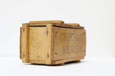 CHOCOLAT MENIERのアンティーク木箱。当時は、この箱にチョコレートを入れて販売していました。コンテナをミニチュアにしたその愛らしさで、現在でも非常に人気が高く、コレクターが多い事もうなづけます。  手の平に乗る小さな箱ですが、きちんとアンティークの佇まいそして存在感があります。アクセサリーなどの小物収納はもちろん、インテリアのアクセントにもどうぞ。