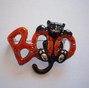 """ハロウィーン(Halloween)のアクセサリーです。  """"BOO""""はおどかしている擬態語です。  クロネコの部分はエナメルで色づけされています。BOOの文字はガラスの七宝のような表面にラインストーンの粒を置いているとても凝ったブローチです。  この商品は未使用の現行品です。  ◆ サイズ: H 30 x W 40 mm  ◆ 刻印: なし  ◆ 状態: 新品の未使用品です。"""