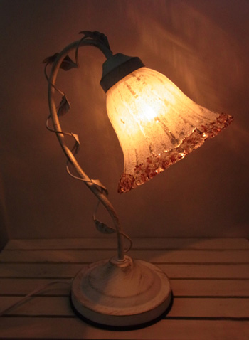 お花のようなオシャレな卓上ランプです。 照明は暖かい落ち着いた感じの色です。 ツルと葉っぱも付いていて面白いデザインです。 シェードの模様が明かりに反映されて、とても綺麗です。 3段階の明るさがあります。 明かりのON、OFF、段階の調整は金属部分をタッチするだけで、とても簡単です。 寝室のサブ照明等、落ち着いた空間作りに適しています。