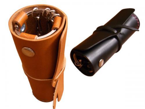 オリジナルデザインのシンプルな革製の円筒型キーケースとなります。  立てて置いておくことが出来ます。 革紐で巻いて閉じるようになっています。 鍵取り付け用ナスカンが4つ付いています。  ※写真サンプル 左) 革:キャメル ステッチ:ナチュラル 右) 革:黒 ステッチ:赤
