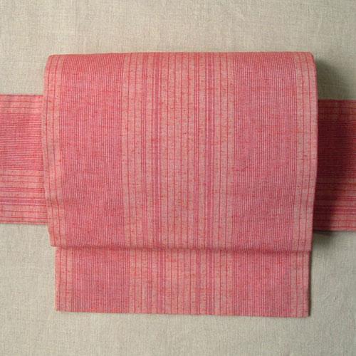 ピンク色の縞がとても可愛いつけ帯です。 遠州木綿を使用し、三河帯芯を入れて仕立てました。 胴に巻く部分とお太鼓になる部分の二つのパーツで出来ているシンプルな二部式帯です。胴パーツを結ぶ紐はモスリンの腰紐を使用しています。 遠州木綿はざっくりとした手触りが心地よく適度な摩擦があるので、着付けの際にずるずると滑る事もなく着物を着慣れていない方にも扱いやすい素材です。