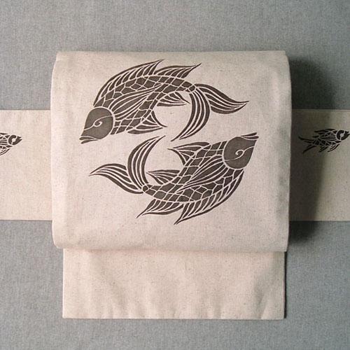 綿麻キャンバス地を使い、型染めをして仕立てたつけ帯です。 当店の完全オリジナル。この柄のつけ帯は他にはございません。 沖縄の壷屋焼に描かれている魚の文様をヒントにデザインいたしました。 民芸のテイストを感じていただけましたら幸いです。 双魚文は縁起の良い吉祥文。末永く楽しい着物ライフにお役立てください。
