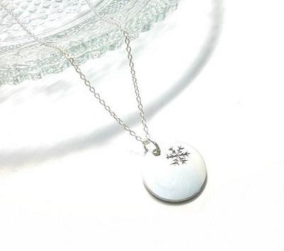 円形のペンダントトップに雪の結晶を一つ彫金しています。  シンプルなデザインですが、雪の結晶がワンポイントになっていて飽きの来ないデザインです。   シルバーアクセサリー工房アンクではオーダーメイドのシルバーアクセサリーの制作も可能です。