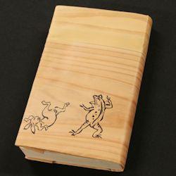 吉野杉を薄くスライスし 同じく薄く漉いた紙を貼り合わせて作った 木目の美しいブックカバーです。  絵柄は、国宝「鳥獣戯画」 京都高山寺の至宝で、 日本最古の漫画といわれる動物たちが 木目の上で戯れる姿は、 日本土産としてもおススメです。  文庫本、新書本を個性的に彩ってください。