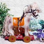 可愛らしい白い木馬のぬいぐるみです。 目やたずなの装飾にビーズが使用されており、尻尾や鬣部分には紐の布が使われています。足元の土台部分は木で出来ており、木馬は布とフェルトが使用されています。 愛らしい顔立ちの木馬で、ディスプレイにも素敵です。