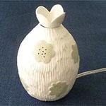 陶芸作家 魚谷あきこさんのアロマライトです。 お花の模様の入った白磁のアロマライトです。上部のオイル皿にお好みのオイルをいれて香りをお楽しみください。