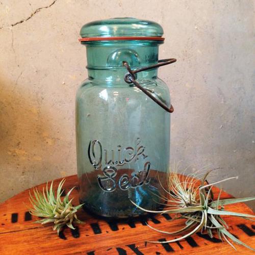 BallジャーやATLASジャーと同じ形をしたガラス保存瓶。 ロゴは、Quick Seal PAT D JULY 14 1908 ブルーのガラスがとても綺麗で 窓際に置くとキラキラと存在感を放ちます。 フタはワイヤーで固定するタイプです。 サイズはクォート(Quart/0.946リットル)。 ビンテージ品特有のサビや細かな傷等ございます、ご理解の上ご購入くださいませ。