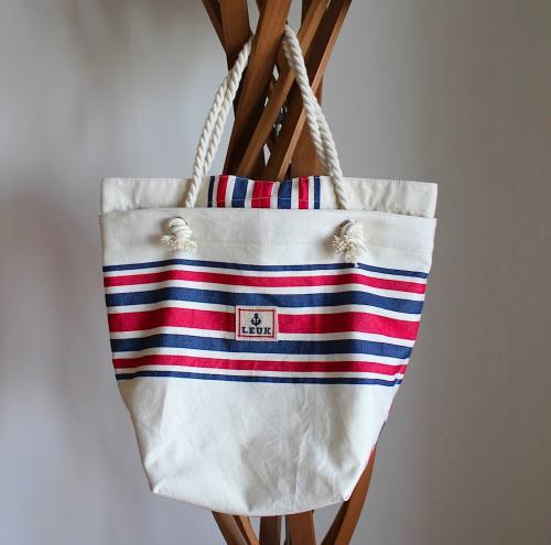 フランスバスク地方のコットン生地を使用したマリンバッグです。 オフホワイトの地にブルー×レッドの爽やかな色合いで、デニムや白いTシャツなどのコーディネートと相性も良く、サマーシーズンに活躍してくれる一品。 雑誌やペットボトルが丁度納まるくらいのサイズ感で、内側にはポケットが2つ付いています。 口元の天マチ部分のボタンで開閉出来る作りとなっており、バッグの中身が見えないようになっています。 ロープのハンドルは肩にかけられる長さになっており、ある程度荷物を入れて頂いても持ち運びしやすくなっています。