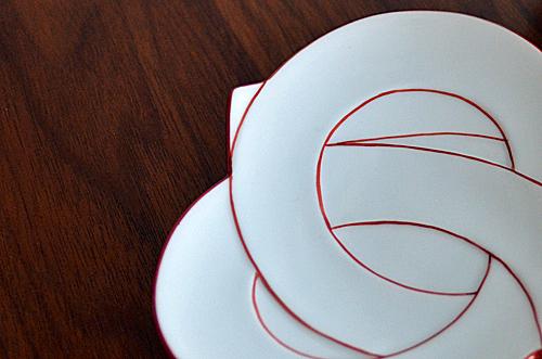 お祝いの席やおもてなしにぴったりな結びの器。  まるで器ごと結んだような形状の銘々皿。 白磁に朱色の縁取りは洗練された印象です。  縁取りは全て手描き。 繊細な技術が深みのある器に仕上がっています。  白と赤とのコントラストはお祝いの席を一段と盛り立てます。 おもてなしにお出ししたら、ホストの心遣いが伝わりそうですね。  お正月からお誕生日まで・・・そして様々なパーティーにも。 器を使うために、パーティーの予定が増えそうな予感です♪
