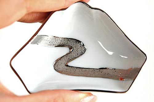 日本のシンボルともいえる富士山の形。 ぱっきり綺麗な白地にプラチナの流水模様が艶やか。 高級感を演出しています。 お正月や晴れの日のうつわとしても彩りを添えます。  時は室町、朝廷で手元に塩を盛る器として発展した手塩皿(てしおざら)。 長じて「おてしょ皿」とも呼ばれます。  4寸(約12�)以内の大きさに形や絵付け、装飾などの技術を施した、小さな小さな芸術品は 江戸時代以降は貴族や大名に愛されました。  江戸時代有田で多く造られた手塩皿は、この度復刻プロジェクトとして現在によみがえっています。  前菜、デザート、ジャムやバター、薬味入れ、箸置きやスプーンレスト、アクセサリートレイなど 使い方も様々。  こちらの富士山型は色違い・柄違いもあります。 コレクションとしてもぜひどうぞ。