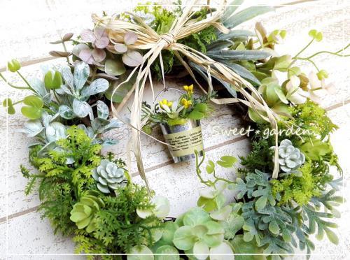 ◆新芽のようなやわらかいグリーンをベースに、黄色や白の小花を入れたかわいいブリキのバケツをぶら下げました。 ミニリースのいいところは、ちょっとしたスペースにちょこっと飾れること! ちょっぴり小さめサイズでも、お部屋にやさしい風を運んできてくれそう・・・。  ※こちらはご注文をお受けしてからの制作となります。 花材の仕入れ状況により、メインではない一部の花材が若干変更になる場合がありますが 同じイメージでの仕上がりになるようにお作り致します。ご了承くださいませ。  ※SOLD OUTになっている場合でも、花材が揃えば再販になります。  ***************************************** スウィートガーデンの無料サービス ***************************************** ◆無料で商品に以下のお好きな香りをプラスできます。   *やさしいローズの香り   *深いラベンダーの香り   *爽快なティートゥリーレモンの香り   *さわやかなベルガモットの香り  箱を開けた時によい香りがすると、何だかうれしいもの・・・。 箱を開けた時にフワッ〜と香る程度ですが、お楽しみいただければうれしいです!  ◆無料でプレゼント用ラッピング&メッセージをおつけできます。 透明フィルムにカーリングリボン&ゴールドのシールで、かわいくラッピング! プレゼント用でご利用の場合は、オリジナルカードにあなただけのメッセージを添えてお届けできます。