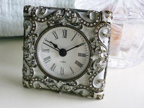 ピューター合金製で、所々にランストーンが煌めく綺麗なアンティーク調の置時計です。 後ろ部分のふたはマグネット式で閉まる様になっています。ふたつきなので後ろから見てもエレガントです。 同じシリーズのフォトスタンドもあります。