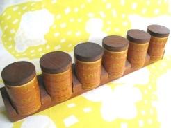 北欧のビンテージ雑貨、イギリスのミッドセンチュリー雑貨、アメリカのコレクタブル雑貨をお届けしているNutmeg Vintageのおすすめ商品!  Xmas Sale-全品1割引です!  ホーンジーのサフランシリーズのスパイスラック。 木のラックもついている珍しいもの。  それぞれのキャニスターはPeppercorn, Clove, Cinnamon, Allspice, Ginger、Nutmegの6種類です。 ものによっては少しの貫入と、蓋に若干変色が見られるものもありますが全体的にコンディションは良好。 中のゴムパッキンも健在、ぴっちり蓋が閉まります。