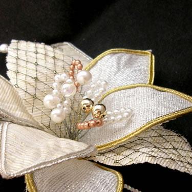 ユリのような花びらを多彩に装飾し、中心のミックスパールと共にバランスよく 組み合わせた、シャープで繊細なコサージュです。  とても高級感があり、フォーマルな場面やパーティーなどで、主役になれるコサージュです。