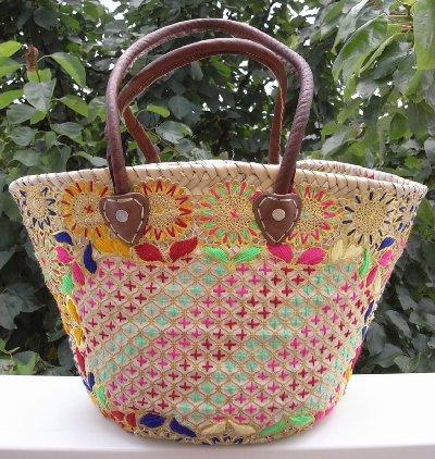 スークではヤシなどの材料を手で編んだ「かごバッグ」がたくさんぶら下げられています。 こちらはひまわりの図柄をもとに様々な色で刺繍が施されたかごバッグ。ビビッド系の元気な色合いです。 フチに革はありません。  このバッグは肩にかけることができますし丈夫な作りですので、暑い夏には活躍してくれそうです。