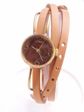 文字盤の数字や留め具など細かなところまで丁寧に手作りした時計です。3重にぐるぐるっと巻きつける、アクセサリー感覚でつけていただけます。文字盤の表面の塗料を焼いてだす「焼き模様」はその時々で異なり同じ物はふたつとありません。  シンプルなデザインですが使い込むほどに色が変わる個性的な腕時計です。