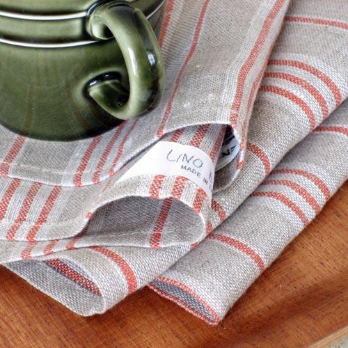 """""""毎日の暮らしを楽しむためのリネン""""として、ご紹介したい リネンのキッチンクロス。 こちら 「リーノ・エ・リーナ 」のリネンは、良質の麻の産地 リトアニア の、 歴史あるリネン工場で 丁寧に作られています。  リネンをキッチンでお使いただくことの良さは、たくさん。  まずは、強いこと!お洗濯に強く丈夫なリネンは、コットンに比べて2倍の強度。その強度は、水分を含むと さらに増します。いつも清潔に保ちたいキッチン周りでのクロス。毎日ゴシゴシ洗っても、へこたれ にくいんです。  吸収性に優れていること、通気性が良いため 乾きやすいのが ◎。  嫌な繊維くず、無し!洗った食器の水分を拭き取るときに 残りがちな、細かい繊維くず が付きにくいのです。  拭いた汚れのシミも、お洗濯で離れやすい!などなど・・・・。  使い続けていくと その感想は、""""古くなっていく"""" というより、""""仕上がっていく""""感覚。汚れたって すり切れたって、まだ手放したくな〜い!!と思えるクロスになるんです。 お使いいただいたら、きっとわかっていただけると思います。  タップリ拭ける大判サイズ。 上質な肌触りの良さ を活かして、手作り小物を作ってみてもいいですね。 こちらのタイプは、タグが 対 で2ヵ所に付いていますので、例えば2枚に切り分けて 小さめクロスに縫い直し 、お使いいただくこともできるんです。  この他にも、ショップではリネンのキッチンクロスを数種類ご紹介していますので、ご覧ください。"""