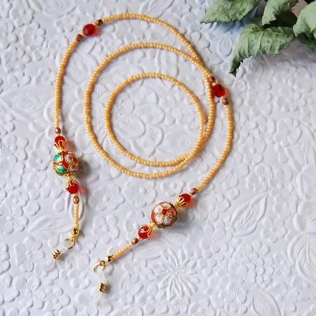 長さは、留め具を含めて約67cmです。  中にはテグスが通っています。  赤地にお花と葉っぱの模様が鮮やかな美しい七宝のビーズ(約12mm)を2個・チェコファイヤポリッシュ(3mm・6mm)・金属パーツを使用しています。  全体的に個性的で華やかなアジアンカラーに仕上げました。  メガネチェーンは、メガネを一時的に首に下げられるという実用性だけでなく、メガネをかけた時にお顔周りを華やかに彩るアクセサリーとしても素敵だと思います。  また、サングラスにも是非どうぞ☆
