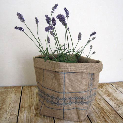 ざっくりした織りの、自然素材 ジュート麻 プランターカバーです。自然素材の風合いを生かして手作りされています。  ナチュラルな麻にブルーの小花がさりげなくて、飾るお花やグリーンを引き立てます。 買ってきたばかりの 味気ないプラスチック苗ポットも、これに入れるだけで、すぐに素敵に飾れますね♪  鉢を入れてカバーとして使うほかにも、いろいろ使えるマルチなポット。  グラスなどの容器に切り花を挿して入れ、フラワーベース風に使っても。 張りがあり しっかりした作りで 自立しますので、小さな シャベルやグローブ といった ガーデニンググッズをまとめて入れるバッグとして。 常温保存のお野菜をストックしたり、小物の整理に フリーボックスとしても、いろいろ便利!!多用途にお使いいただけます。  入れ口に 折り返しがあり、深めに使いたいときは 返し部分を伸ばして使用できます。 内側にはビニールコーティングが施されていますが、水やり時にはカバーから出して作業をしてください。  陶製などのプランターカバーは、使用しないときには かさばり がちですが、 このカバーなら、収納時にはコンパクトに折りたためて場所もとりません。 ナチュラルで かわいい上に 機能的。マルチなアイテムです。  こちらは、3サイズあるうちの、Lサイズです。